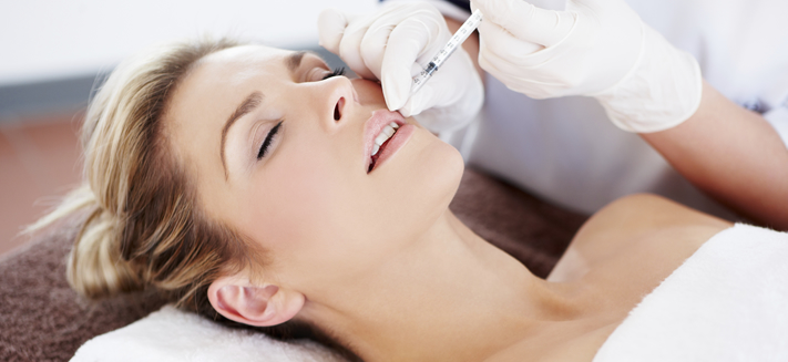 A woman has lip fillers - dermal fillers from Elan Medical Skin Clinics in central London and Essex can help improve smiles